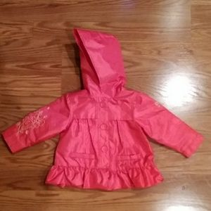 Pink hooded jacket with flowers on sleeves.